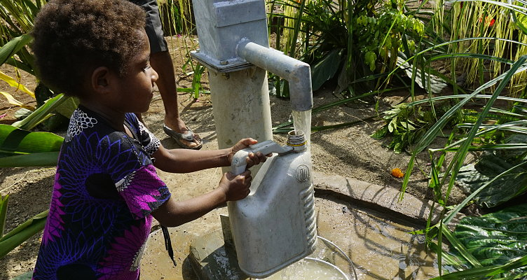 papua new guinea child gets drink of clean water